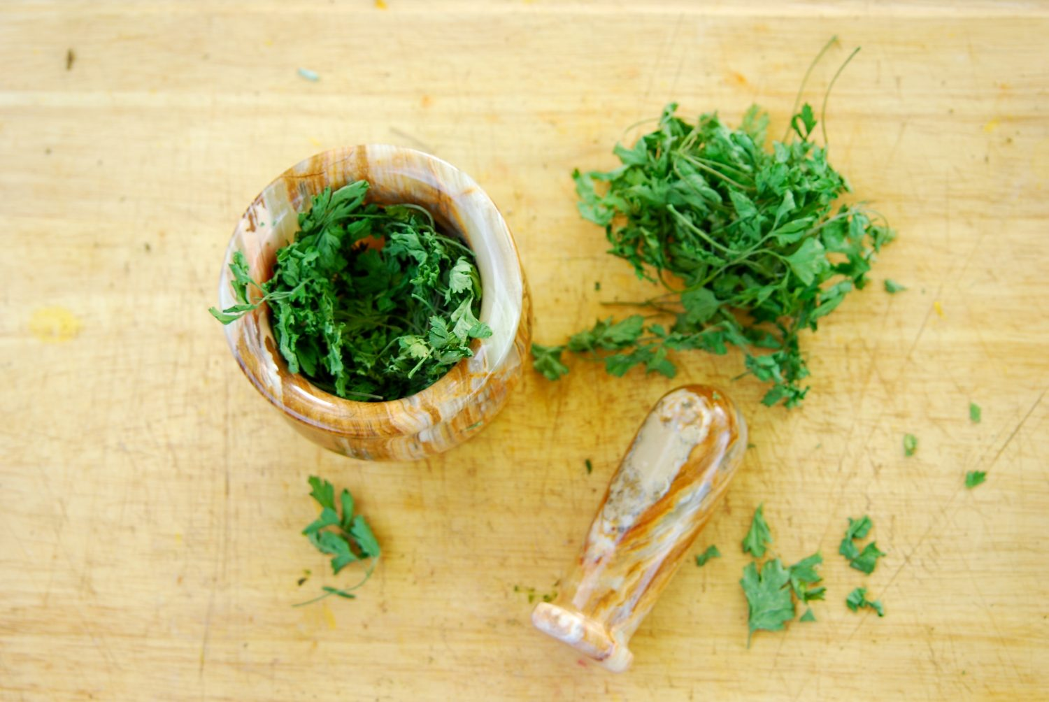 Top down view of dried parsley next to and inside of a mortar and pestle.