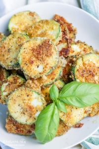 Fried parmesan zucchini on a plate garnished with basil.