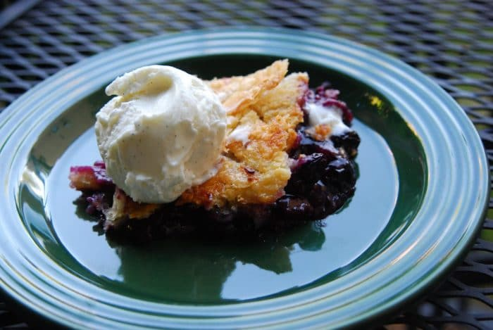 Slice of blueberry and peach cobbler on a plate topped with vanilla ice cream.