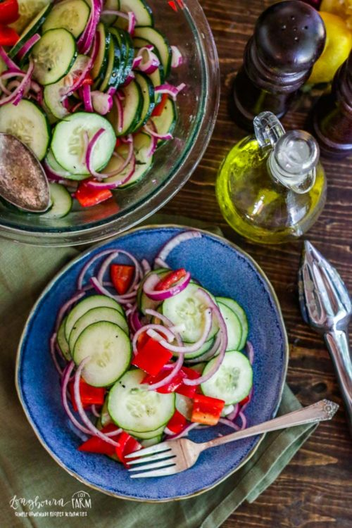 Easy cucumber salad next to an olive oil container and a bowl of easy cucumber salad.