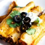 Close-up of three beef enchiladas topped with cilantro, sour cream and olives.