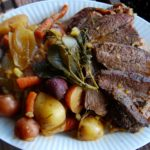 Easy pot roast sliced on a platter with roasted root vegetables on a plate.