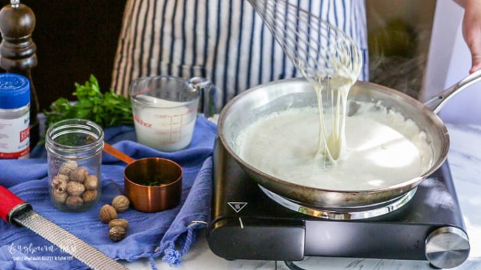 Cheese pull with a whisk from finished easy homemade alfredo sauce.