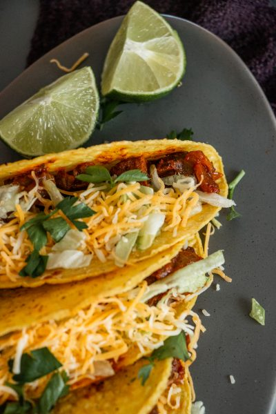 upclose view of cheese covered steak tacos with lime wedges to the side