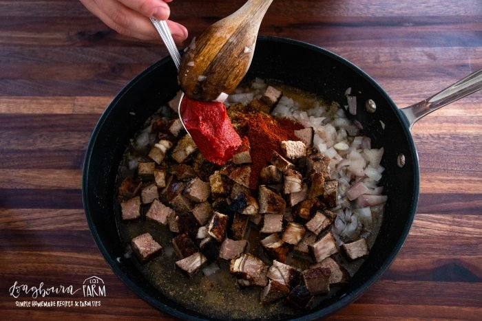 using a wooden spoon to scrape in a spoonful of tomatoe paste to the steak mixture