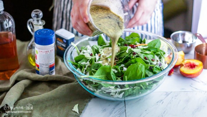 Pouring creamy poppy seed dressing over the quick spinach salad.