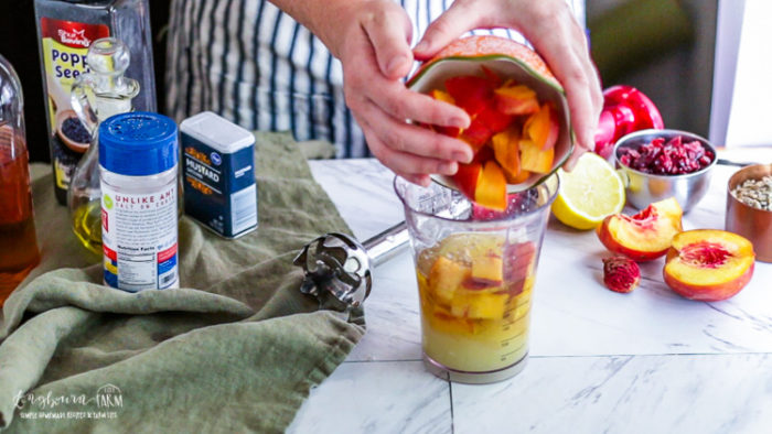 Adding peaches to the creamy poppy seed dressing.
