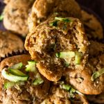 a pile of baked zucchini muffins with some shredded zucchini scattered on top