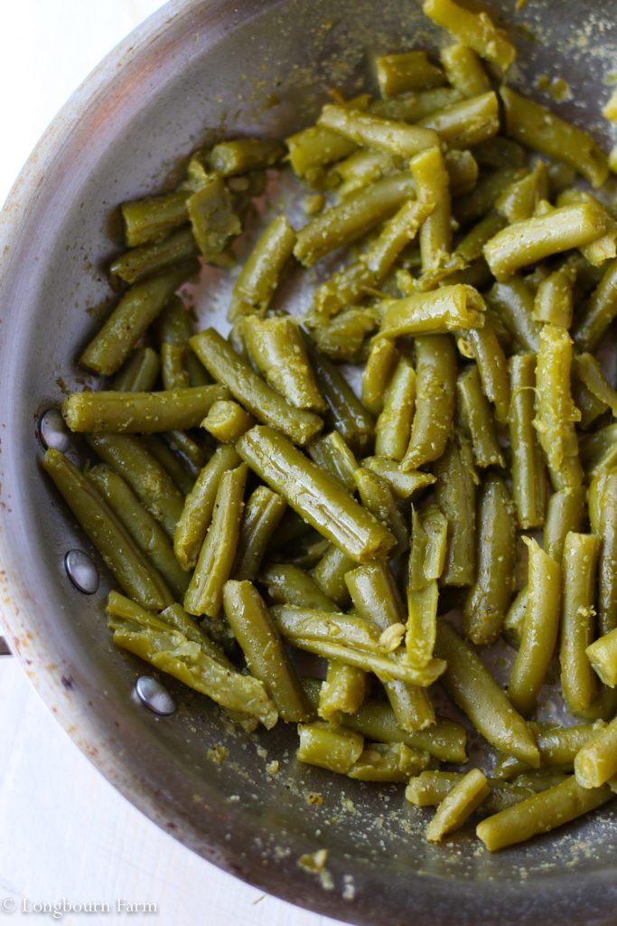 Cooked canned green beans in a pan.