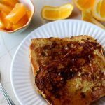 Easy french toast on a plate with syrup next to a bowl of oranges.