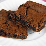 Two brownies made from homemade brownie mix sitting on a plate.