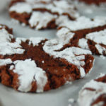 Close-up of chewy chocolate crinkle cookies on a sheet tray.