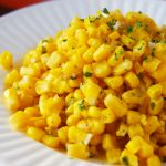 Cooked canned corn piled on a plate.