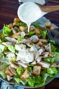 spooning caesar salad dressing onto salad