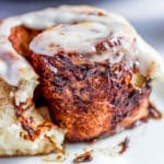 Baked and iced homemade cinnamon roll on a white plate.