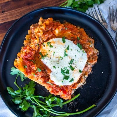 aerial view of a slice of red lasagna on a dark plate with fresh parsley