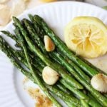 Roasted asparagus on a plate topped with roasted garlic cloves next to a lemon half.