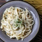 Quick alfredo pasta recipe in a bowl with dry noodles and parmesan in the background.