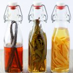 Front view of three lined up bottle of homemade vanilla extract, homemade mint extract, and homemade lemon extract.