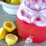 Vat of raspberry lemonade next to spent lemon halves.