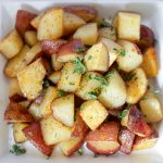 Crispy roasted potatoes on square plate.