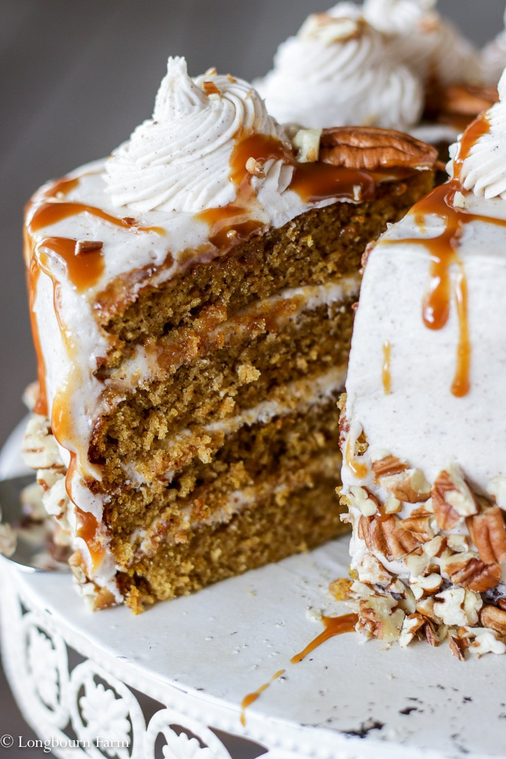 Pulling a slice of layered pumpkin spice cake out of the cake.