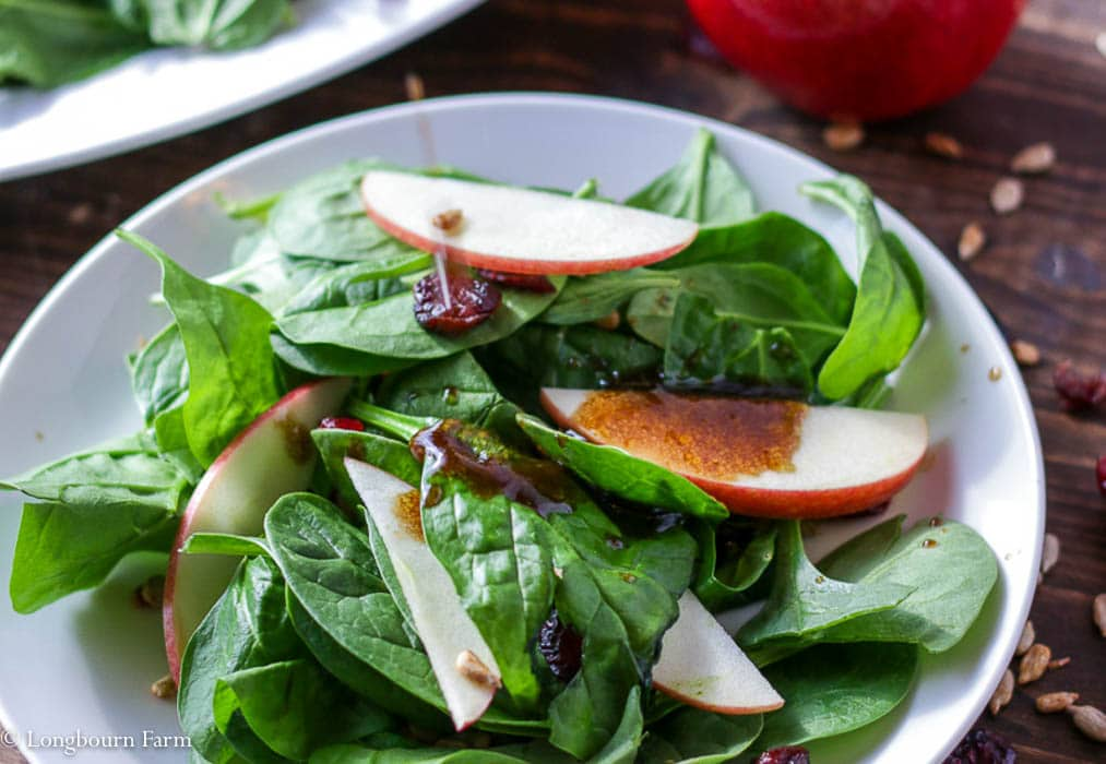 Dressed spinach and apple winter salad on a plate.