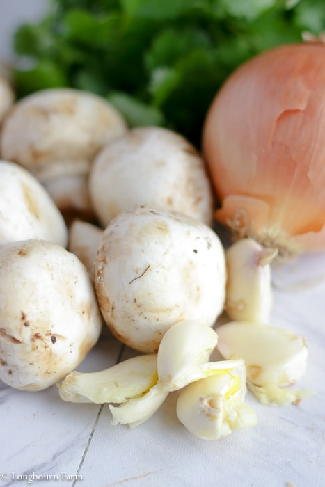 Loose garlic cloves next to a small onion and a pile of mushrooms with parsley in the background.