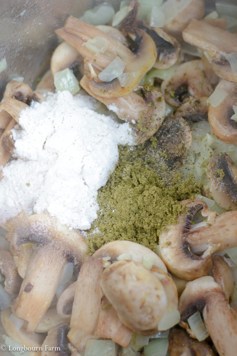 Spices and flour on top of sautéing mushrooms and onions in an Instant Pot.
