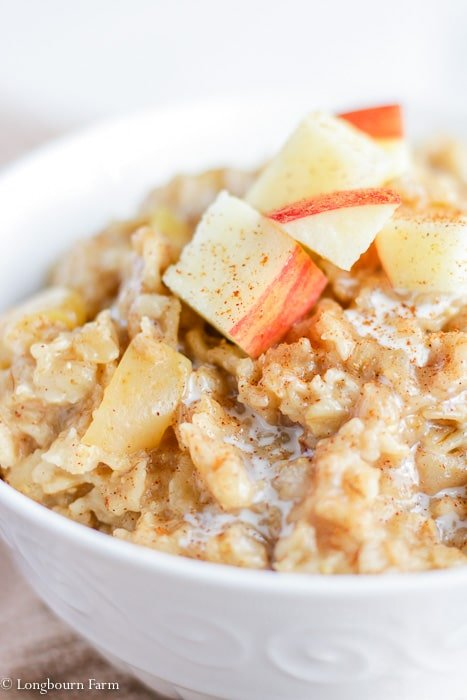 Cooked apple cinnamon instant pot oatmeal in a white bowl garnished with fresh apples.