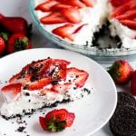 Horizontal image of a slice of no bake strawberry cheesecake on a plate with strawberries and Oreos nearby with the whole cheesecake in the background.