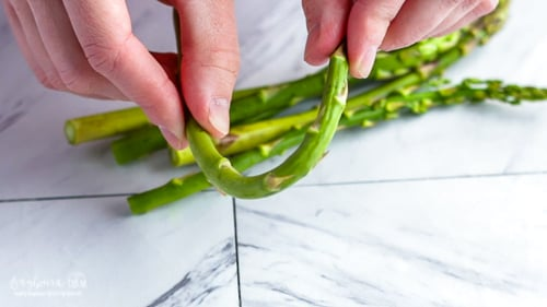 Showing how to trim asparagus by bending an asparagus spear to break it.