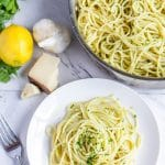 Spaghetti with lemon cream sauce in a stainless steel pan next to a plate of spaghetti with lemon cream sauce with parsley bunch, lemon, cheese, and a garlic head nearby.