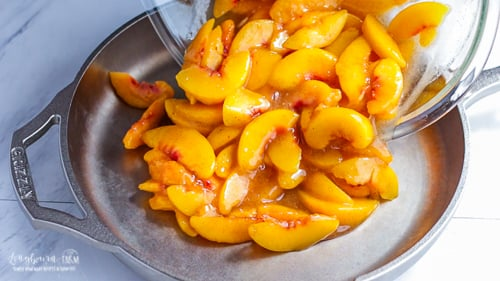 Pouring peaches into the GRIZZLY Cast Iron skillet for easy peach cobbler.
