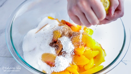 Squeezing lemon juice into peach mixture for easy peach cobbler.