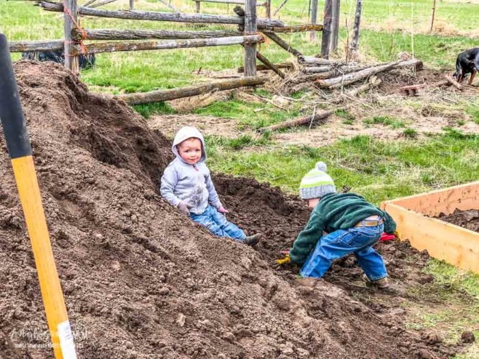 Kids playing on sandy loam soil pile for raised planter garden boxes.