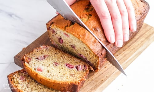 Knife slicing a loaf of strawberry banana bread.