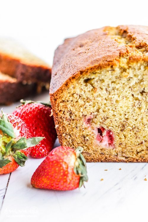 Close-up of cut side of the loaf of strawberry banana bread next to a few loose strawberries.