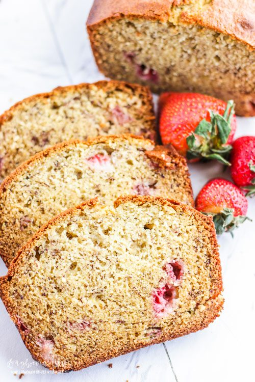 Three slices of strawberry banana bread next to some loose strawberries.