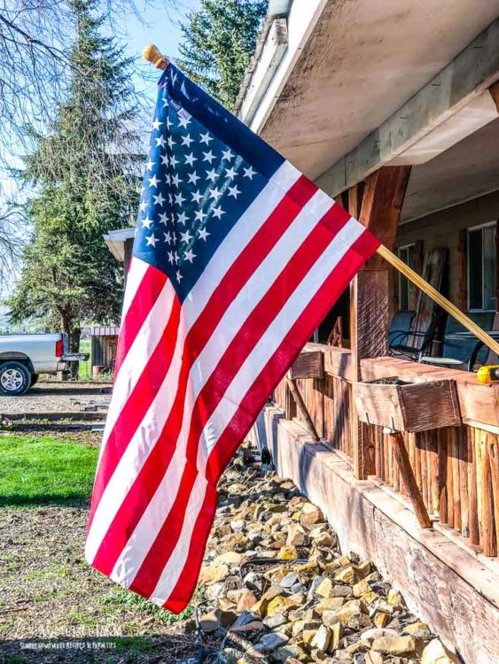 American flag hanging on the front of a wood porch.