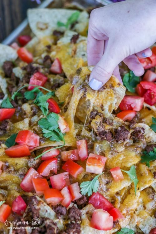 Pulling a cheesy ground beef nacho off of the tray.