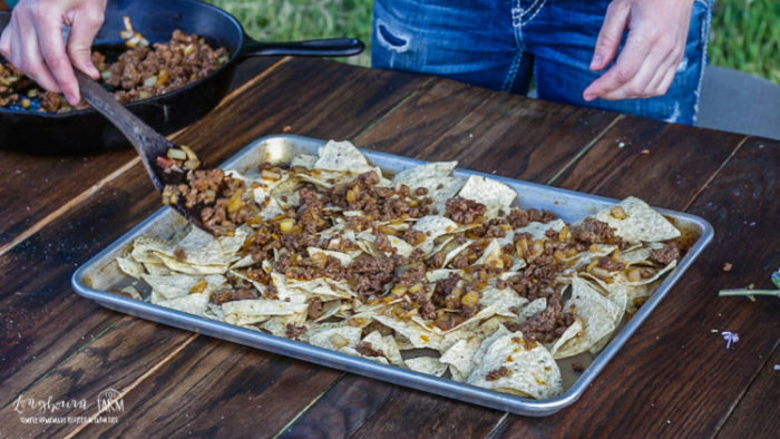Spreading meat mixture over the tortilla chips for ground beef nachos.
