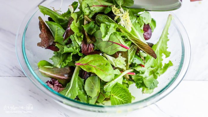 Pouring spring greens into a glass bowl for lemon salad dressing and easy green salad.