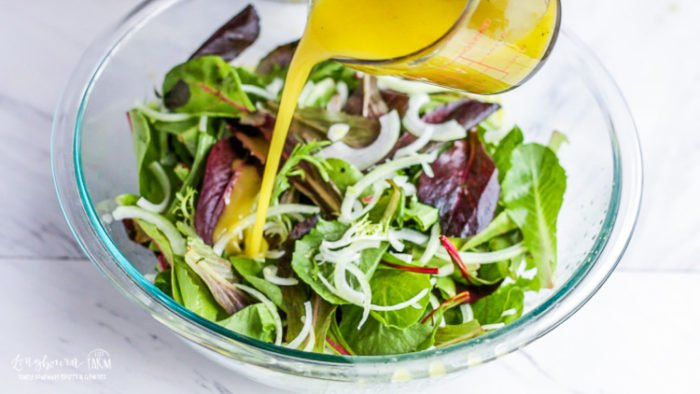 Pouring lemon salad dressing over easy green salad.