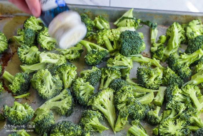 Sprinkling garlic powder onto broccoli.
