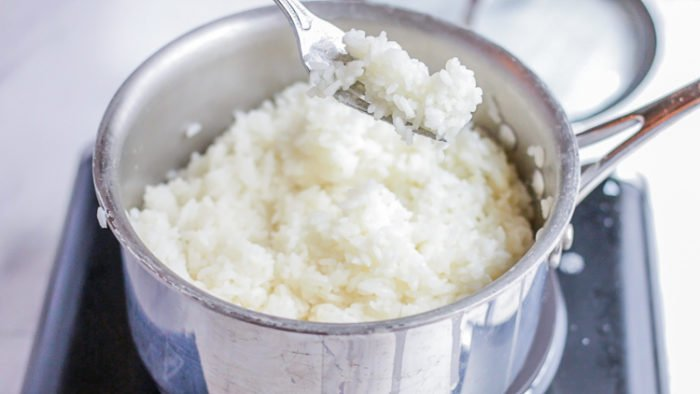 Finished white rice recipe with white rice on a fork.