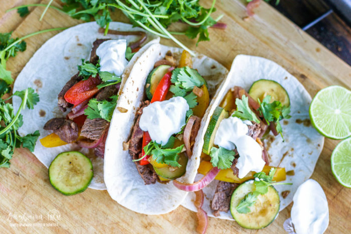 Horizontal view of steak fajita recipe on tortillas topped with sour cream and cilantro.