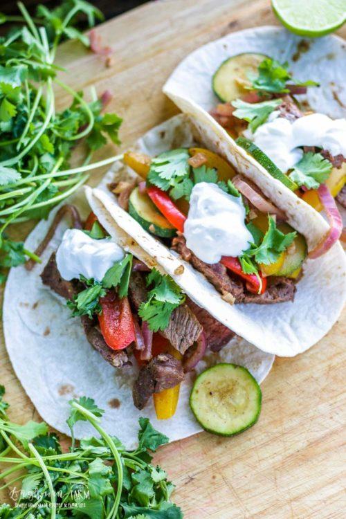 Three fajitas made from beef fajita recipe on a cutting board with sour cream on top.