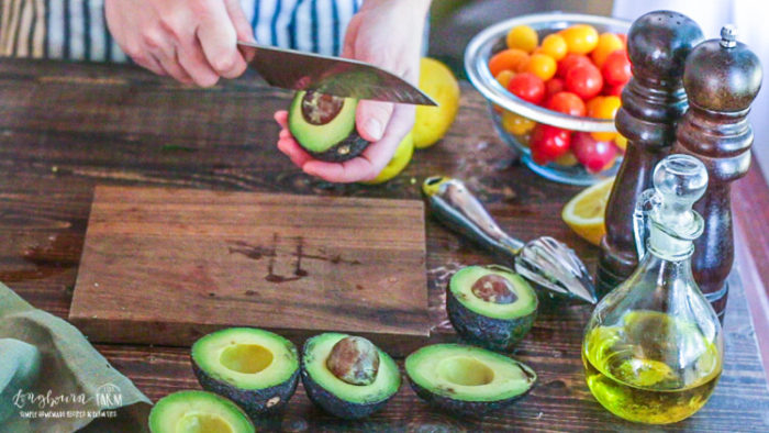 De-pitting an avocado with a knife.