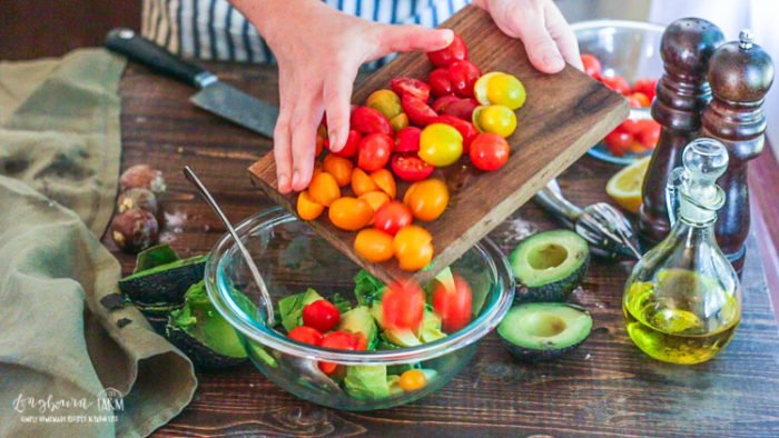 Sliding tomatoes into the avocado salad bowl.